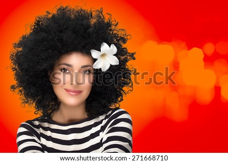 Beauty Hair care. Fashion Model Woman Portrait with Healthy Curly Afro Hairstyle and Lily Flower in Hair. Fashion portrait on orange and red background with copy space - stock photo