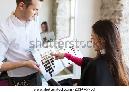 beauty, hair dyeing and people concept - happy young woman with hairdresser choosing hair color from palette samples at salon - stock photo