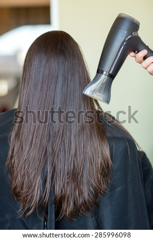 beauty, haircare, blow-dry, hairstyle and people concept - stylist hand with fan dries woman hair at salon - stock photo