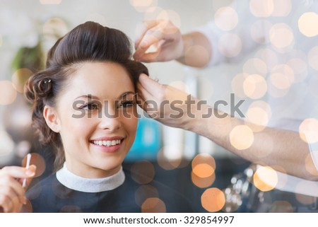 beauty, hairstyle and people concept - happy young woman with hairdresser making hairdo at salon over holidays lights