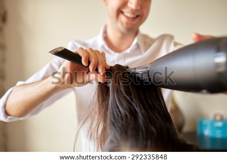 beauty, hairstyle, blow-dry and people concept -  close up of hairdresser with fan and brush making hot styling at hair salon - stock photo