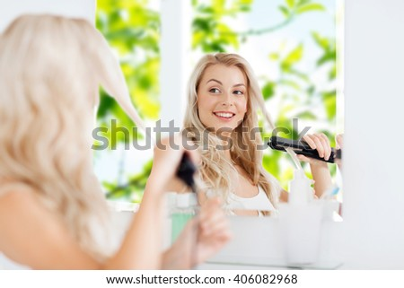 beauty, hairstyle, morning and people concept - smiling young woman with styling iron straightening her hair and looking to mirror at home bathroom over green natural background - stock photo