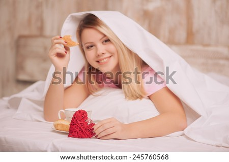 Beauty having breakfast in bed. Young woman sitting in bed with coffee and eating croissants served to bed due to valentines day, selective focus on rustic gift hearts - stock photo