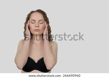 Beauty, health, make up and skin care concept - Young woman makes facial massage on gray background with copy space for advertising text - stock photo