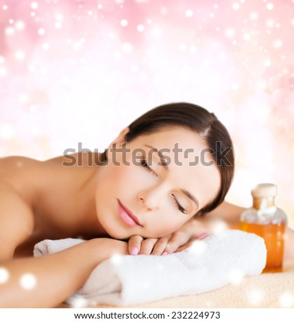 beauty, health, people and spa concept - beautiful young woman with body oil in spa over pink background