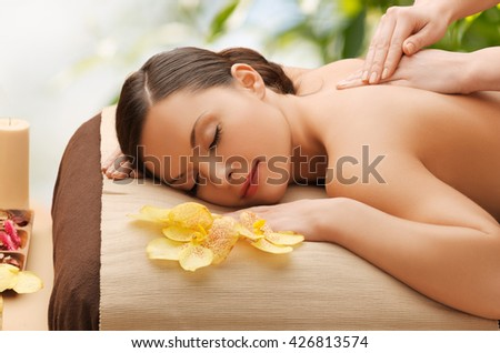 beauty, holidays and spa concept - woman in spa salon getting massage - stock photo