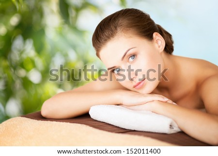beauty, holidays and spa concept - woman in spa salon lying on the massage desk - stock photo