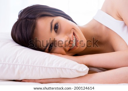 Beauty in bed. Beautiful young smiling woman relaxing in bed and looking at camera