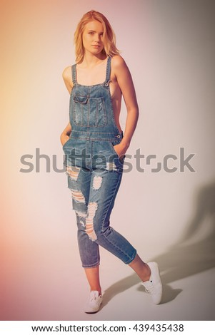 Beauty in denim style. Full length studio shot of beautiful young woman wearing jeans overall over the naked body and looking at camera