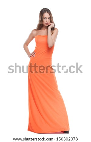 Beauty in dress. Beautiful young woman in orange dress posing while isolated on white - stock photo
