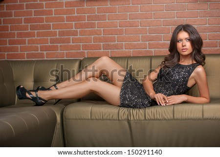 Beauty in gown wear. Beautiful young brown hair woman in formal dress lying on the couch and looking away - stock photo