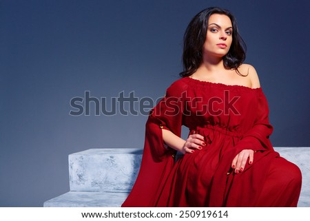 Beauty in marsala dress. Fashion image of beautiful young woman in trendy marsala dress sitting on the stairs on dark blue background - stock photo