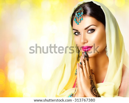 Beauty Indian woman  portrait. Hindu girl hold hands together is symbol prayer and gratitude. Indian model girl with black henna tattoos looking in camera. Mehndi. Indian marriage traditions  - stock photo