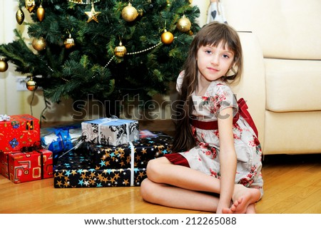 Beauty kid  girl being happy about christmas tree and lights. - stock photo