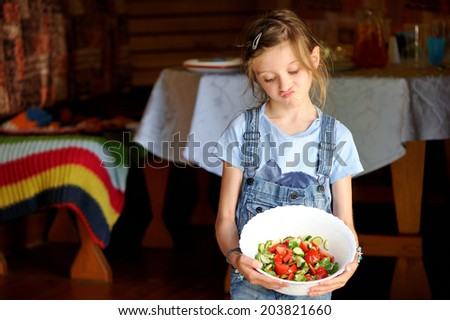 Beauty kid girl holding bowl of homemade fresh salad outdoors in the garden: unhappy girl doesn't want to eat vegetables - stock photo