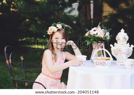 Beauty kid girl in flower wreath having tea in the garden - stock photo