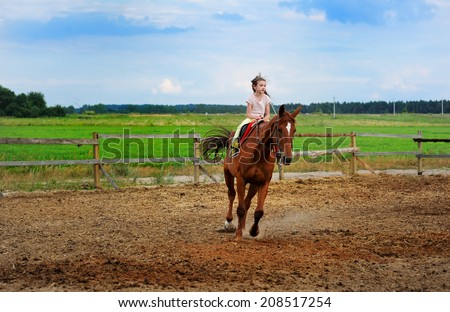 Beauty kid girl with long brunette hair riding a horse  in the farm on the beauty summer day - stock photo