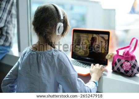 Beauty kid  l girl using laptop and headphones  at airport - stock photo