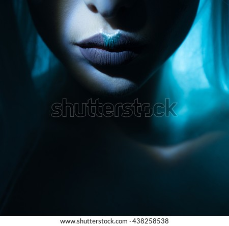 beauty lips with atmospheric light effect comming out of the dark , blue lips with grey - stock photo