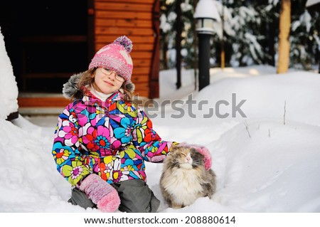 Beauty little girl in colorful winter jacket and hat plays with a furry cat in deep snow on nice winter day
