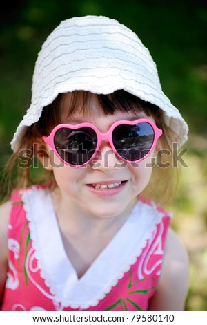 Beauty little girl in white sun hat and heart pink sunglasses smiling