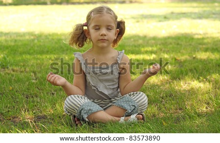 beauty little girl meditating in park - stock photo