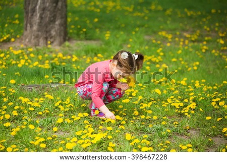 Beauty little girl with yellow dandelions playing outside on spring sunny day. Child sitting in fresh green grass among spring flowers. Small baby girl making bouquet of wild flowers. - stock photo