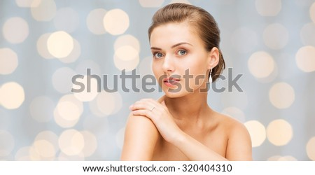 beauty, luxury, people, holidays and jewelry concept - beautiful woman with diamond earrings over lights background