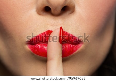 beauty, make up and people concept - close up of woman lips or mouth with red lipstick