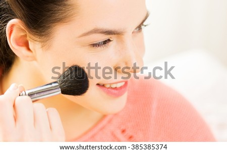 beauty, make up, cosmetics and people concept - close up of smiling young woman face applying blush with makeup brush - stock photo