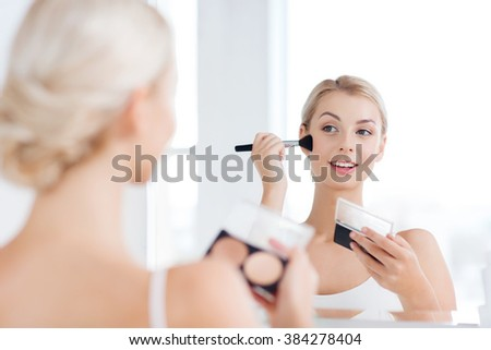 beauty, make up, cosmetics, morning and people concept - young woman with makeup brush and contouring and highlighting palette looking to mirror at home bathroom - stock photo