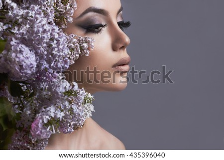 beauty make-up face.Young woman with flowers.Beautiful Girl with lilac flowers - stock photo