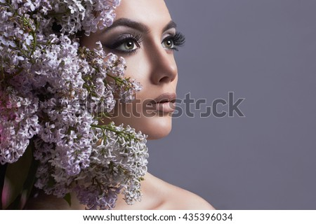 beauty make-up face.Young woman with lilac flowers.Beautiful Girl with long eyelashes.cosmetics - stock photo