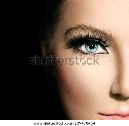 Beauty makeup for blue eyes. Part of beautiful face closeup. Perfect skin, long eyelashes. Make up concept. isolated on black background - stock photo