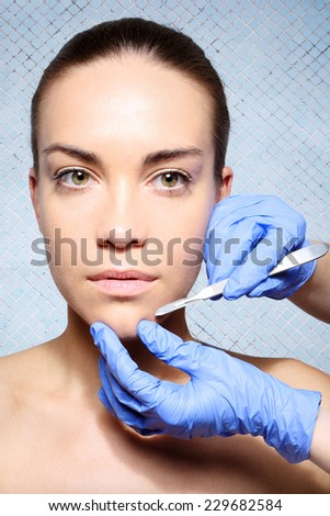 Beauty  medicine, beauty parlor, peeling of procedure.Caucasian woman during surgery using a scalpel - stock photo