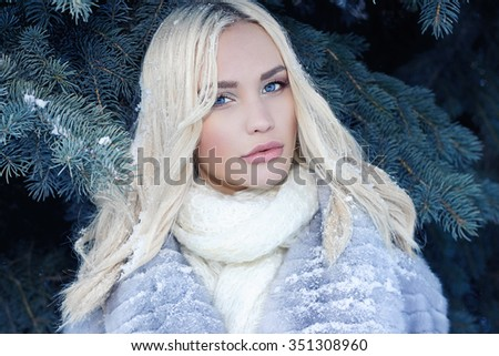Beauty mode girl in winter forest. beautiful young Woman in fashionable Fur Coat and leather gloves. snow on the hair - stock photo