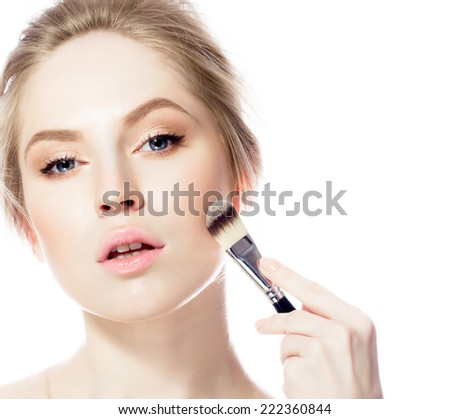 Beauty model applying foundation on her face - stock photo