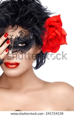 Beauty model girl in black carnival mask and big red rose flower. Red lips and manicure. Glamorous beauty model with creative masquerade eye makeup. Closeup portrait isolated on white with copy space.