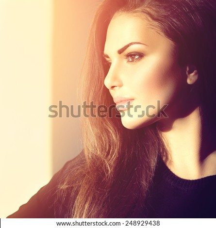 Beauty model girl portrait looking out the window. Young beauty romantic girl looking away, close-up. Beautiful brunette make-up woman in sun light. - stock photo