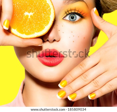 Beauty Model Girl takes Juicy Oranges. Beautiful Joyful teen girl with freckles, funny hairstyle, yellow makeup and manicure. Professional make up. Orange  Slices  - stock photo