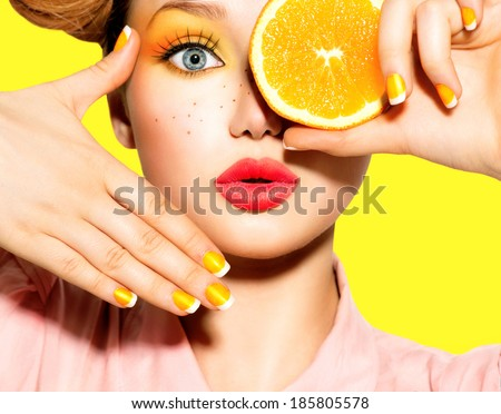 Beauty Model Girl takes Juicy Oranges. Beautiful Joyful teen girl with freckles, funny red hairstyle, yellow makeup and nails. Professional make up. Orange Slices.   - stock photo