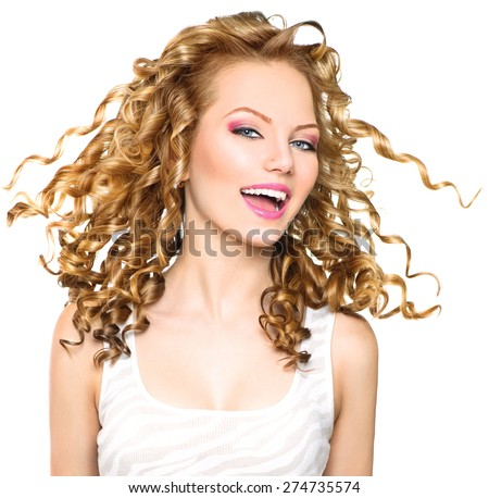 Beauty model girl with blowing Blonde curly hair. Portrait isolated on white background. Healthy wavy hair. Hairstyle. Beautiful smiling young woman. Beautiful face, natural make up. Long permed hair - stock photo