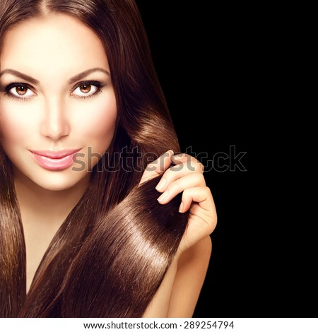 Beauty Model girl with Healthy Brown Hair. Beautiful brunette woman touching long smooth shiny straight hair. Hairstyle. Hair cosmetics, haircare. Hair care, extensions. Isolated on black background - stock photo