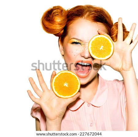 Beauty Model Girl with Juicy Oranges. Beautiful Joyful teen girl with freckles, funny red hairstyle and yellow makeup . Professional make up. Orange Slices. Isolated on a white background  - stock photo