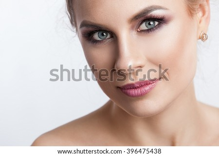 Beauty model girl with perfect make-up isolated over white. Portrait of attractive young woman with blond hair on white background. Beautiful female face with clear fresh skin.
