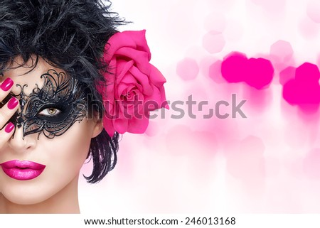 Beauty model girl with stylish black carnival mask. Pink lips and manicure. Glamorous beauty model in creative masquerade eye makeup. Closeup portrait over pink bokeh background with copy space. - stock photo