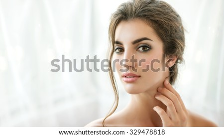 Beauty model with  natural make up, wet hair and fresh skin is posing front of the window. Youth and Skin Care Concept.  Make up and Hair. Morning.  Close up, selected focus. - stock photo