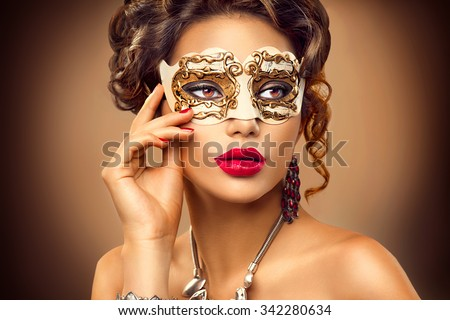 Beauty model woman wearing venetian masquerade carnival mask at party, over holiday background. Christmas and New Year celebration. Sexy girl with holiday makeup and manicure. Red lips and nails  - stock photo