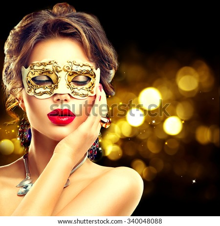 Beauty model woman wearing venetian masquerade carnival mask at party over holiday dark background with magic glow. Christmas and New Year celebration. Glamour lady with perfect make up and hairstyle - stock photo