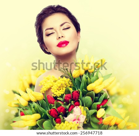 Beauty model Woman with Spring Flower bouquet. Beautiful girl with a Bouquet of colorful Tulip flowers. Happy surprised model woman smelling flowers. Mother's Day. Springtime - stock photo